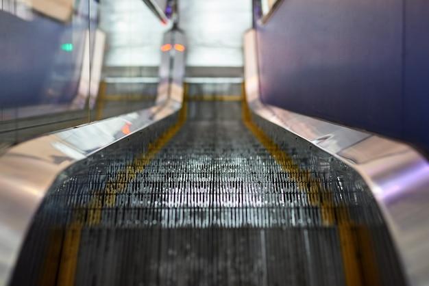 視点でショッピングセンターの近代的な電気エスカレーターの階段をクローズアップ