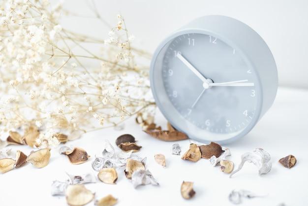 古典的な目覚まし時計、花の枝、白いテーブルの上の花びら。