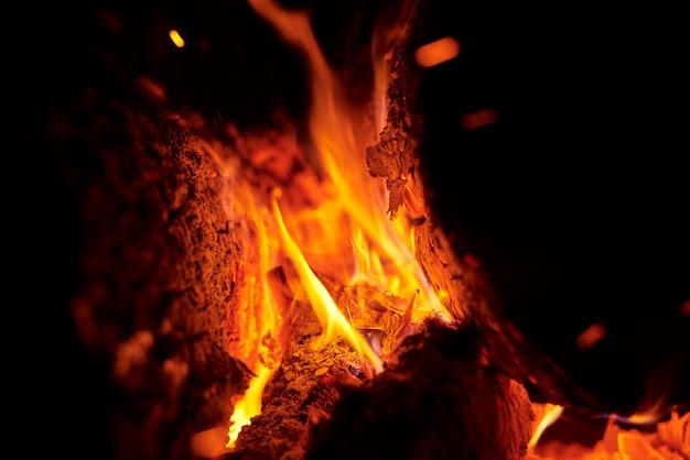 夜の火花でき火のクローズアップ。暗闇の中で丸太や石炭を燃やすことによる熱