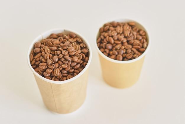 Две бумажные кофейные чашки с кофейными зернами