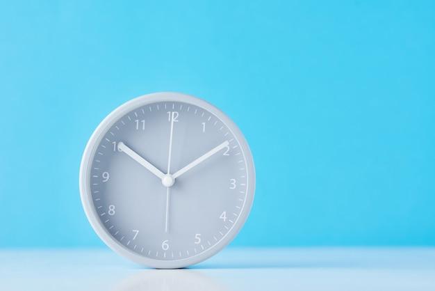 コピースペースとパステルブルーの背景に灰色の古典的な目覚まし時計