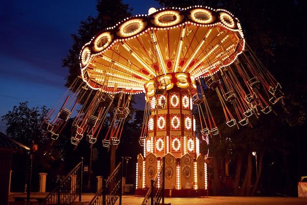 夜の街の遊園地で観覧車の照明