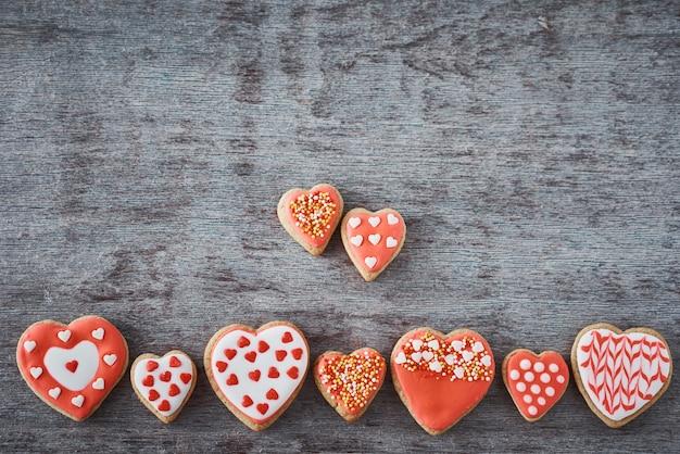 灰色の表面にグレーのアイシングと艶をかけられたハート形のクッキーで飾られ、平らに横たわっていました。バレンタインデーの食べ物のコンセプト