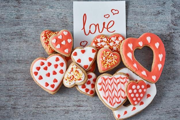 装飾と艶をかけられたハート形のクッキーと灰色の表面、上面に灰色の碑文愛と紙のメモ。バレンタインデーのコンセプト