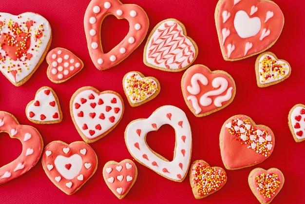 赤い表面にアイシングと艶をかけられたハート形のクッキーで飾られた、フラットレイアウト。バレンタインデーの食べ物のコンセプト