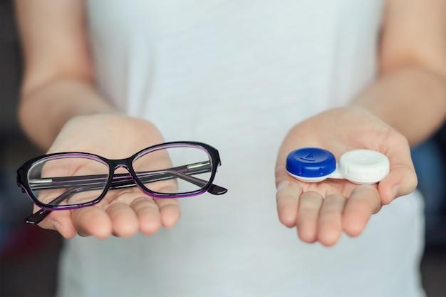 女性はコンタクトレンズとメガネを手で保持します。視力保護の選択の概念
