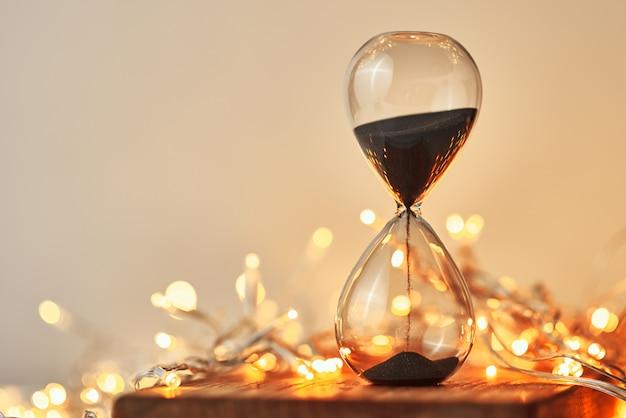 Песочные часы и праздничные огни гирлянды в боке