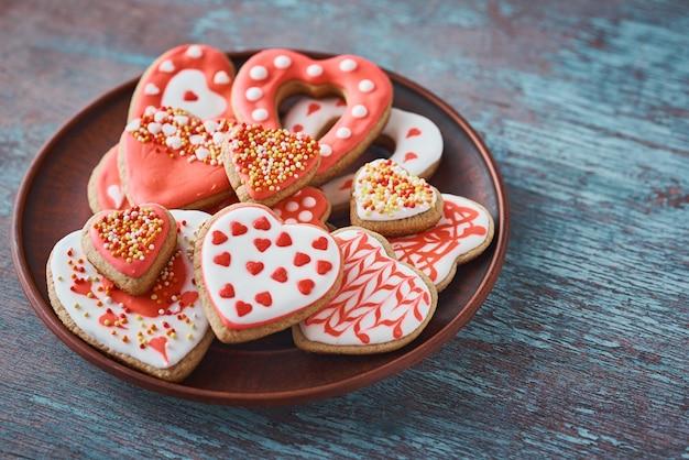 灰色の表面にグレーのプレートに装飾されたハート形のクッキー。バレンタインデーの食べ物のコンセプト