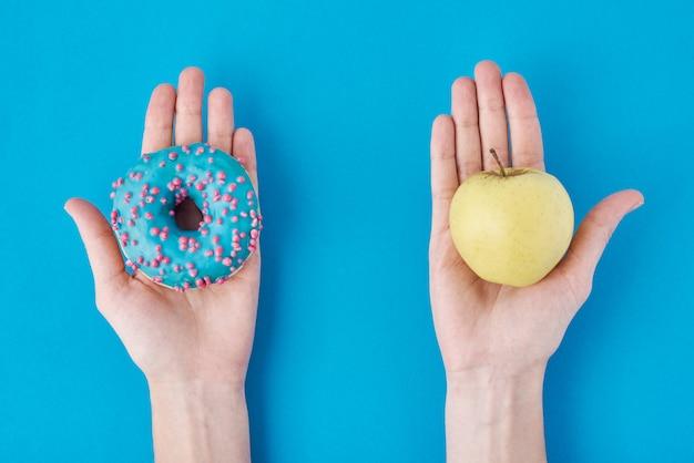 Женщина, выбирая между яблоком и пончик в ее руках. концепция здорового питания.