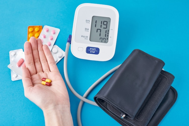 Цифровой тонометр и медицинские таблетки в руке на синем. концепция здравоохранения и медицины