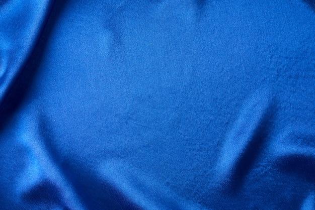 ひだのある青い絹。波状のサテンの表面の抽象的なテクスチャ