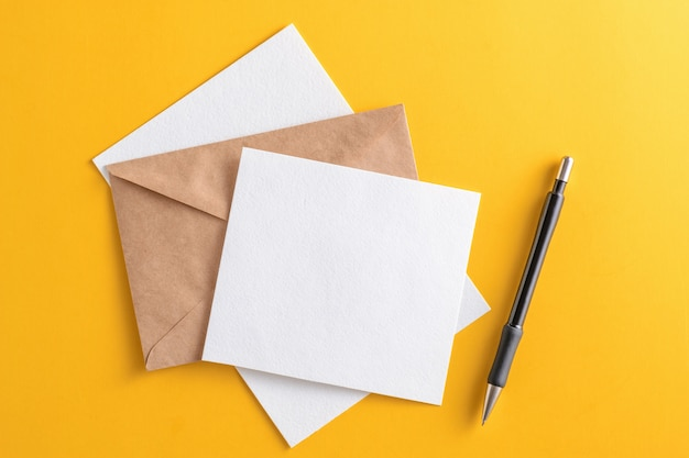 クラフト茶色の紙封筒と黄色の背景に鉛筆で空白の白いカード