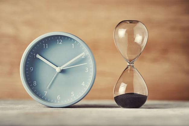 Песочные часы и будильник на столе, крупным планом