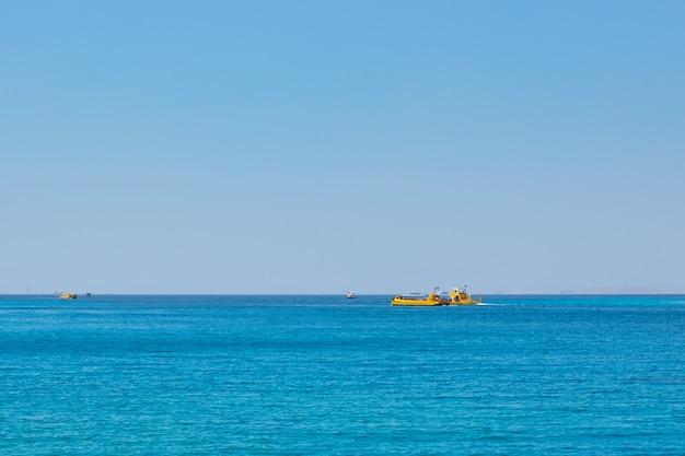 Морской пейзаж с кораблями против голубого неба без облаков