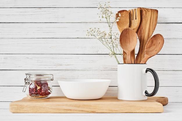 Кухонные инструменты и разделочная доска на белом столе