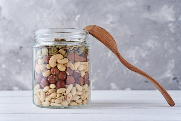 Различные виды орехов и семян в стеклянной банке, крупным планом