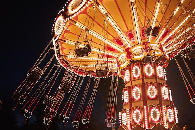 夜の遊園地で照らされたスイングチェーンカルーセル