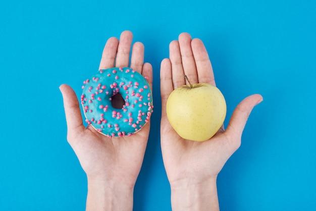 女性は彼女の手でリンゴとドーナツを選択します。健康食品のコンセプト。