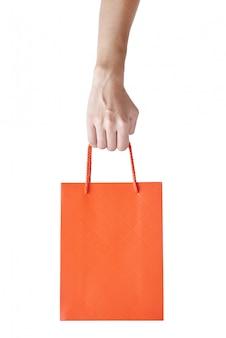 女性の手は、白で隔離赤い空空白クラフト紙ショッピングバッグを保持します。包装テンプレートのモックアップ