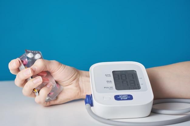 Рука с горсткой таблеток и цифровой монитор артериального давления. концепция здравоохранения и медицины