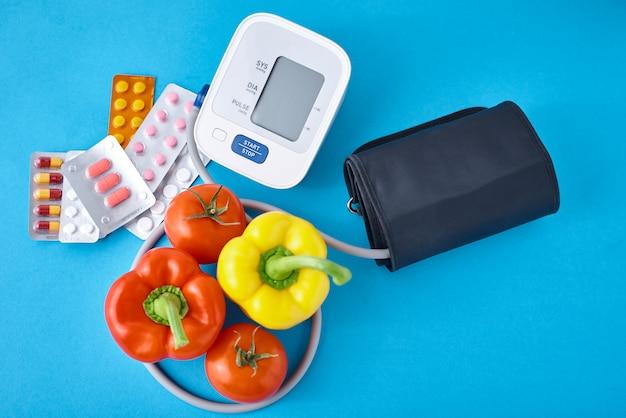 Цифровой тонометр, свежие овощи и медицинские таблетки на синем фоне. концепция здорового образа жизни