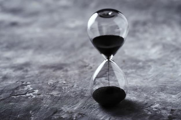 コピースペースで暗い背景に砂時計。時間切れと締め切りの概念