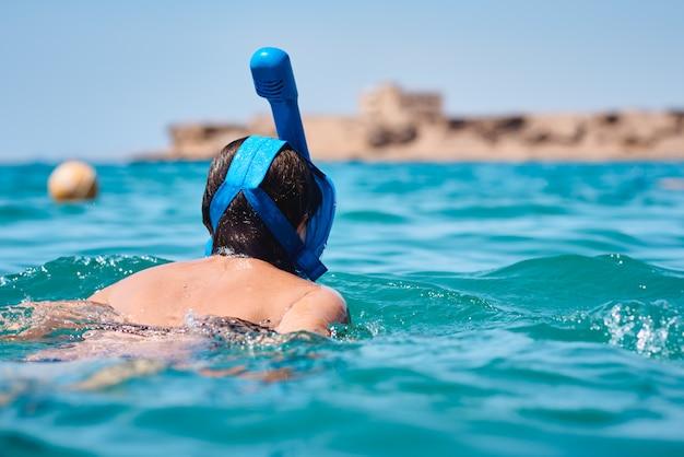 Женщина с подводным плаванием маски полного лица в синем море. летний отпуск