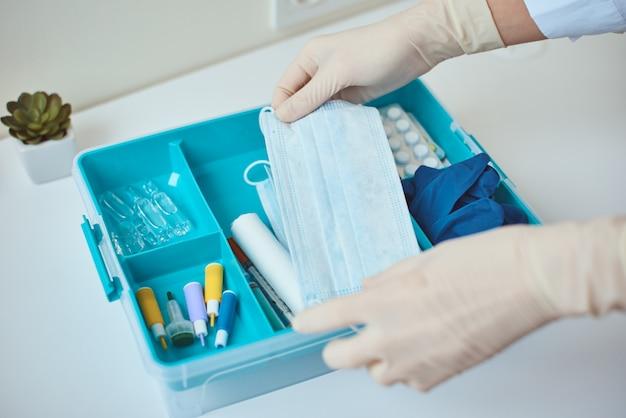 手袋をはめた手は、応急処置キットから保護用ミディシンマスクを取ります。医薬品と在宅医療ボックス。ウイルス保護の概念。