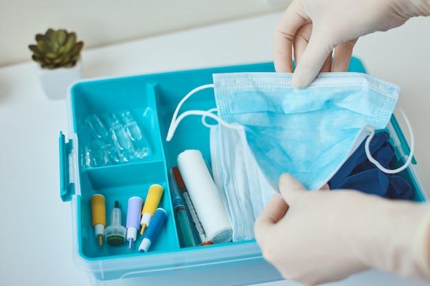 手袋をはめた状態で、救急箱から防護マスクをとります。医薬品と家庭薬ボックス。ウイルス保護の概念。