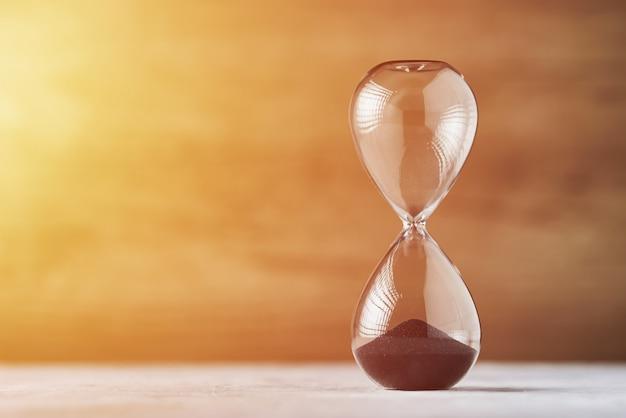 Песочные часы на деревянных фоне с копией пространства. концепция нехватки времени и сроков