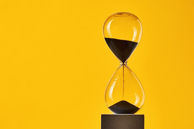 コピースペースと黄色の背景に砂時計。時間切れと期限切れの概念