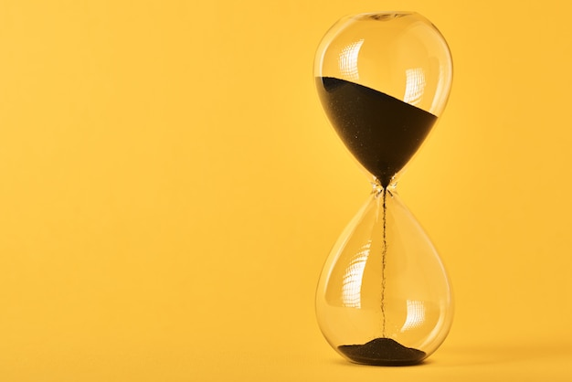 Песочные часы на желтом фоне с копией пространства. концепция нехватки времени и сроков