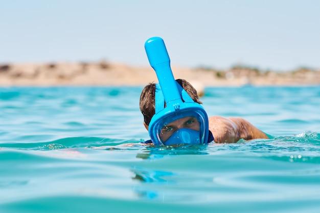 Человек с подводным плаванием маска полного лица в синем море. летний отпуск