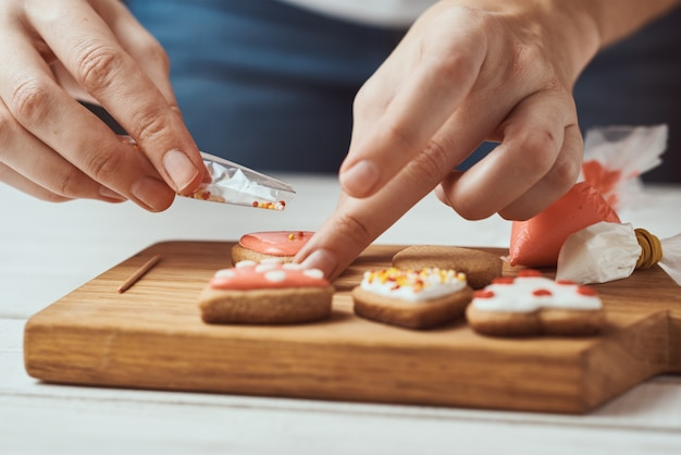 Украшать пряники глазурью. руки женщины украшают печенье в форме сердца, крупным планом