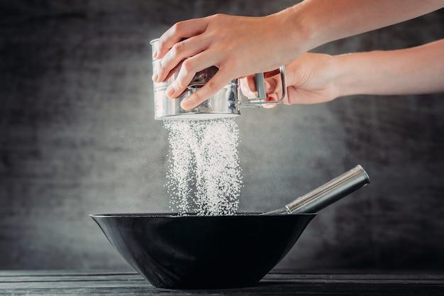 暗い背景に黒のボウルの上にふるいで小麦粉をふるいにかける女性