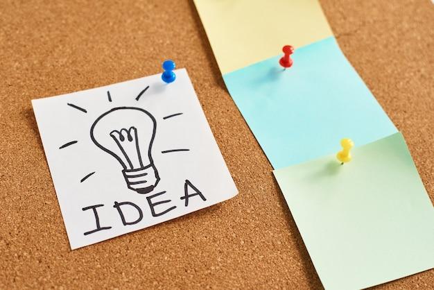 単語のアイデアと色の空白のノートで描かれた電球