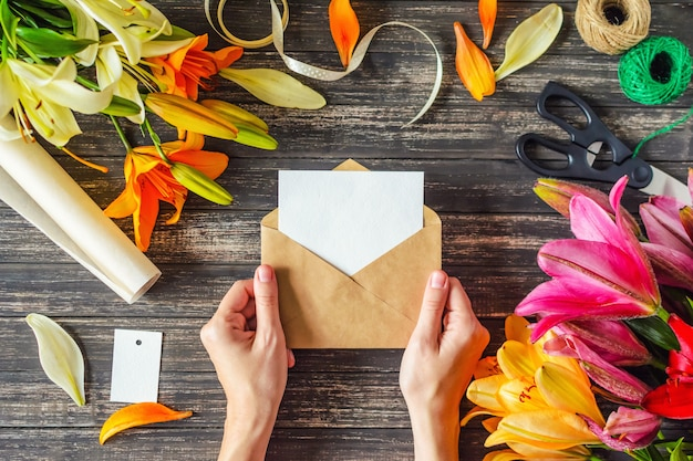 女性の手は白紙の封筒と木製のテーブルの上の花の装飾を保持します。