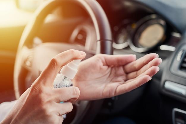 ドライバーは、運転前に車内で抗菌消毒剤を使用して手を消毒します。