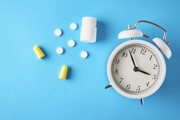 不眠症の問題の概念。目覚まし時計、耳栓、青色の背景、上面に錠剤