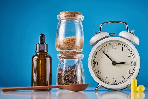 うつ病や不眠症の概念を治療するための漢方薬。目覚まし時計、薬草、青の背景にアロマセラピーオイル