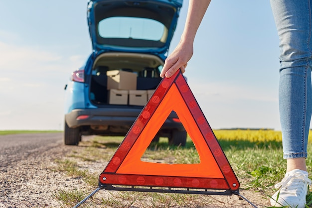 Женщина ставит знак аварийной остановки возле разбитой машины на дороге