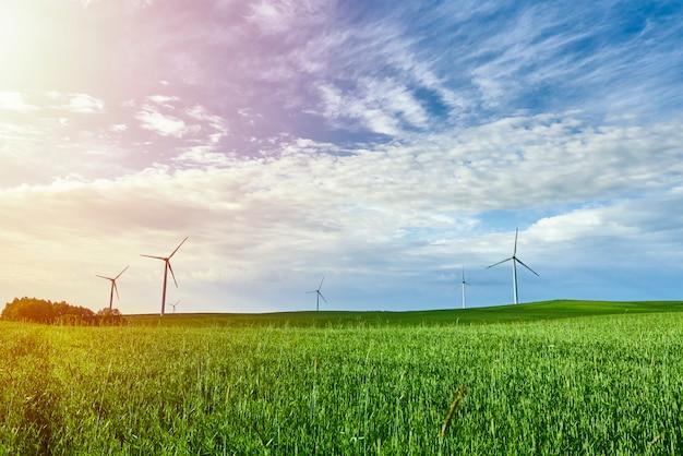 青い空と緑のフィールドの風力タービン