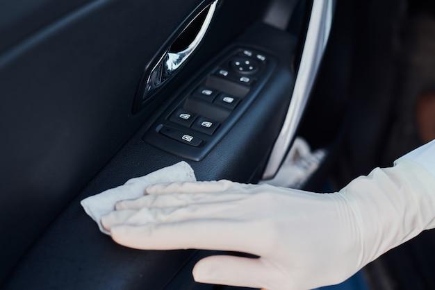 車のインテリアのクリーニング女性。抗菌ワイプ消毒車で手