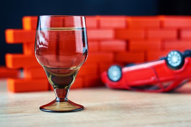 アルコールと運転の概念。ショットグラスと壊れた車