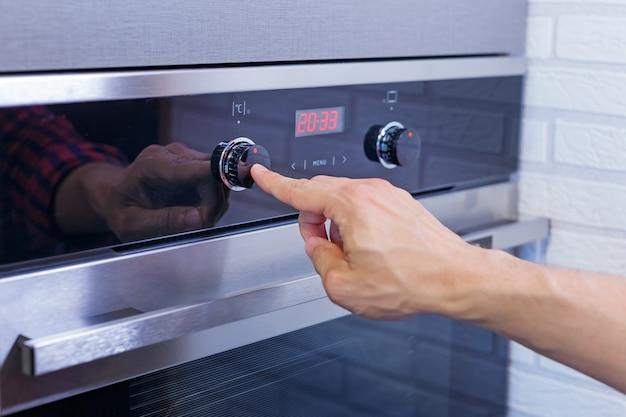 Рука человека, установка режима приготовления пищи на электрической печи.