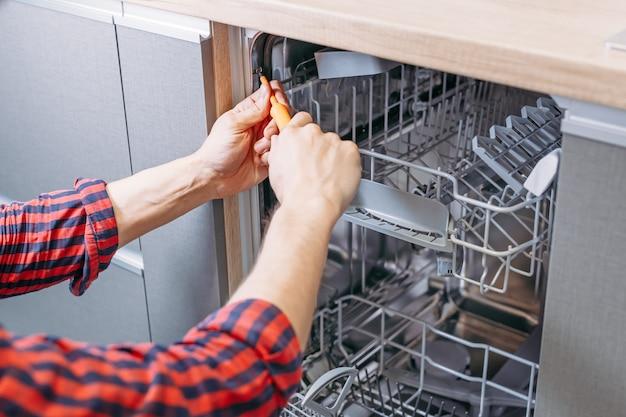 男は食器洗い機を修復します。ドライバーと男性の手はキッチン家電をインストールします