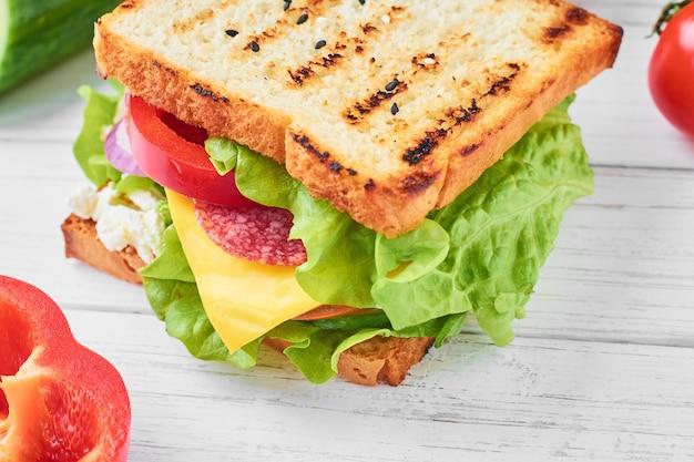 ハム、レタス、新鮮な野菜の白い背景の上のサンドイッチをクローズアップ