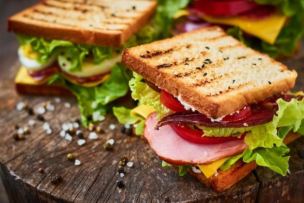 ハム、レタス、チーズ、トマトの木製の背景に自家製サンドイッチ