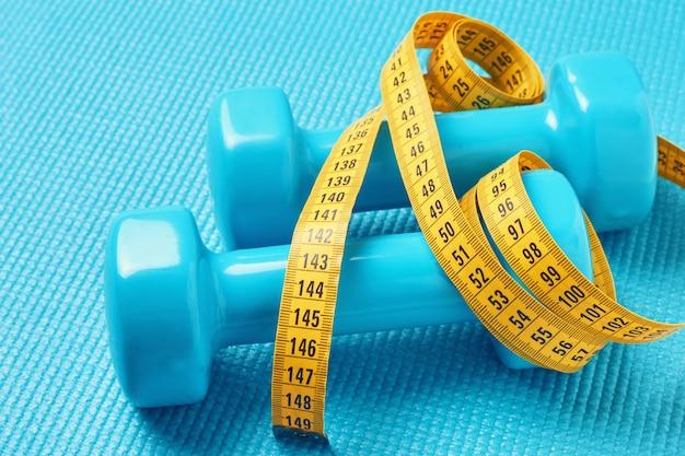 フィットネスの概念ダンベルと青い背景に測定テープをクローズアップ