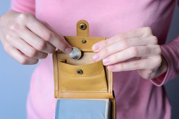 Женщина в розовом свитере кладет монету в открытый кошелек.